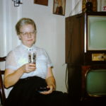 Emma Lou sitting by two stacked TVs at her brother's house in Cadillac, MI